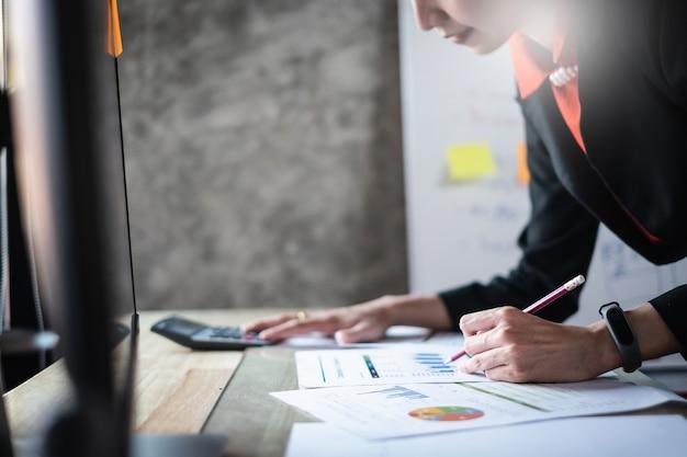 ビジネスの女性のための計算機とラップトップを使用してオフィスで木製の机の上の数学の金融を閉じる