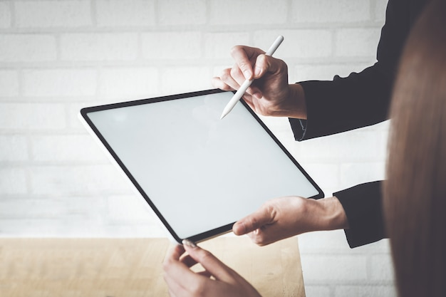 手でデジタルタブレットデバイスを保持している実業家のモックアップ。