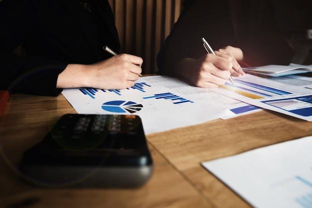Закройте вверх деловая женщина и партнер с помощью калькулятора для расчета финансов, налогов, бухгалтерского учета, статистики и аналитических исследований, групповой поддержки и концепции встречи