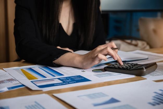 Бизнес-леди используя калькулятор для анализирует с документом данных по запасов концепция финансирования бизнеса.