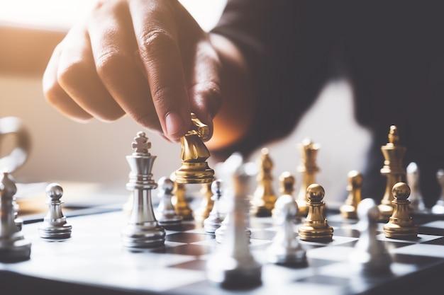 Бизнесмен играя или двигая диаграмму шахмат в игре успеха конкуренции.