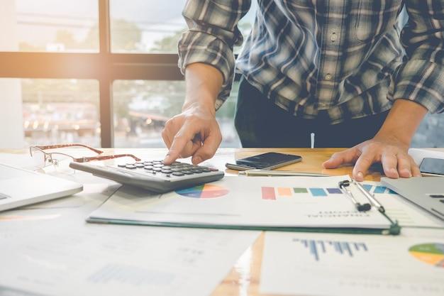 ビジネスマンは、財務用紙、税金、会計、会計士のコンセプトを計算するための電卓とラップトップコンピュータを使用しています。