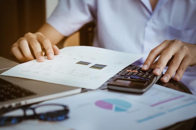 Закройте деловой человек, используя калькулятор и портативный компьютер для расчета с финансовой бумаги, налоговые, бухгалтерский учет, концепция бухгалтера.