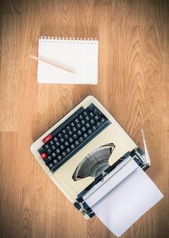 ヴィンテージタイプライターと紙の空のノート