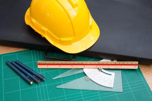 Желтый шлем безопасности и инструменты для рисования