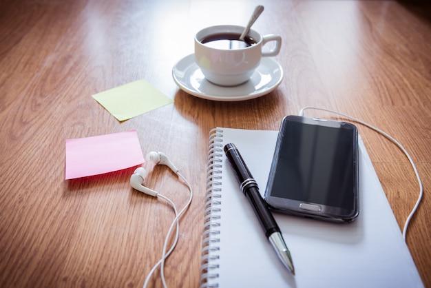 メモ帳、コーヒーカップ、ペン、スマートフォン、ヘッドフォン、付箋付きのオフィステーブル