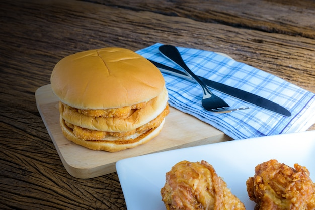 Куриный гамбургер и жареная курица на деревянной разделочной доске с ножом и вилкой, салфетка