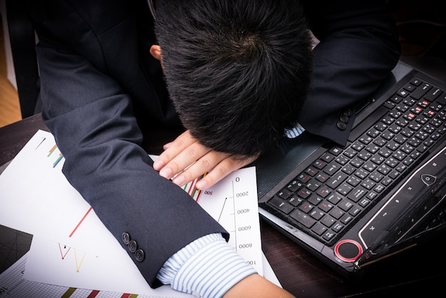 Измученный и уставший бизнесмен, спящий в офисе