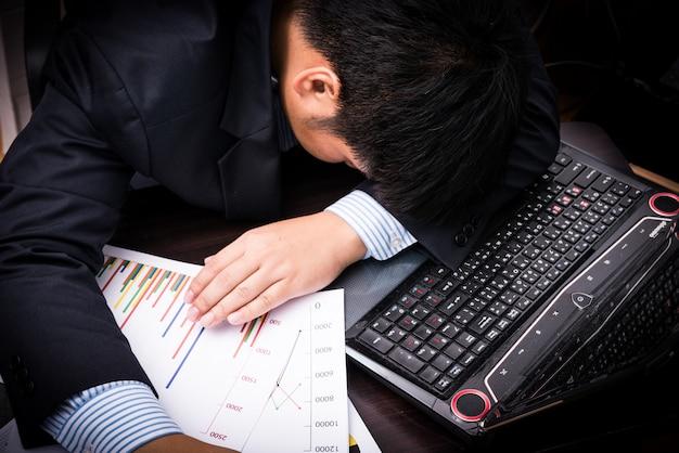 Измученный и усталый бизнесмен спит в офисе