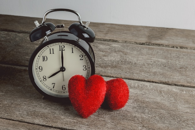 目覚まし時計と木製のテーブル、バレンタインデーの背景にハート形