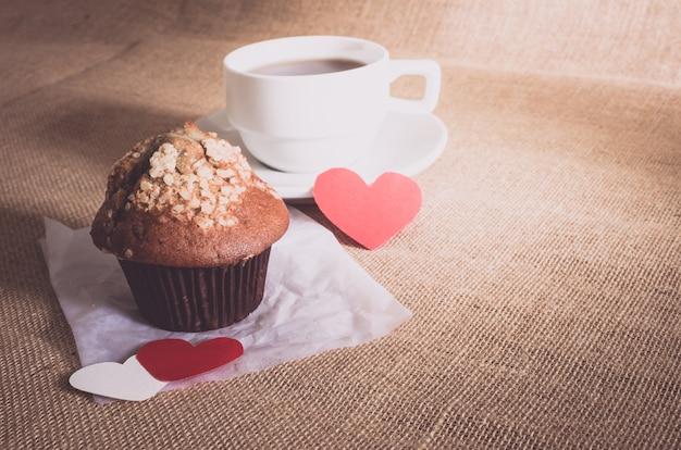 チョコレートのマフィンとコーヒーと荒布テクスチャ上の心