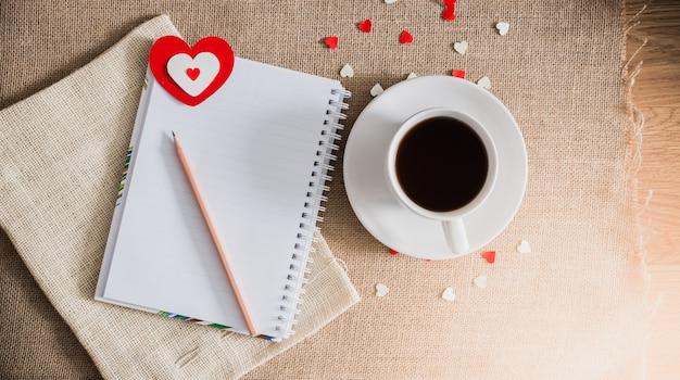 コーヒーカップと荒布テクスチャ上の心