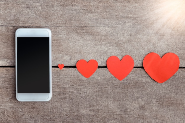 Бумага для смартфонов и сердец на деревянном фоне