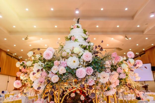 結婚披露宴での花と燭台で飾られたウェディングケーキ
