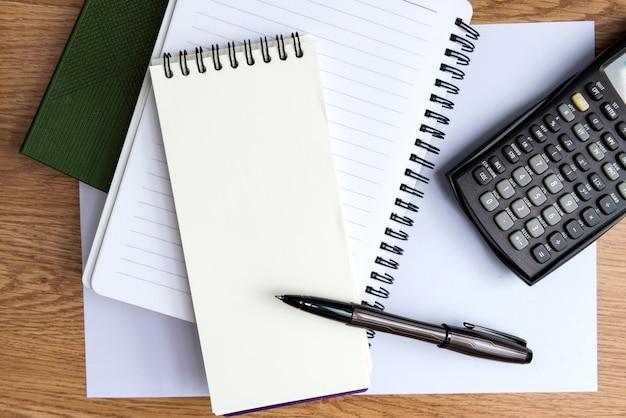 電卓、ペン、木製のテーブルの上のノート