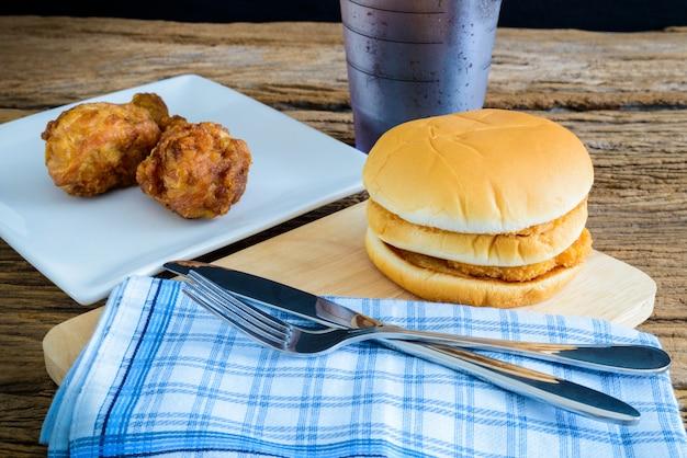 Куриный гамбургер и жареная курица, стакан колы на деревянной разделочной доске с ножом и вилкой, салфетка