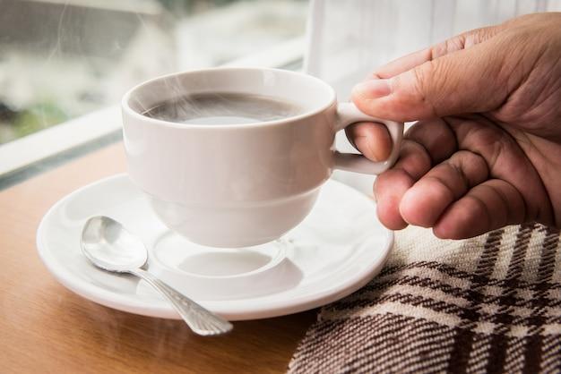 Держа чашку горячего кофе
