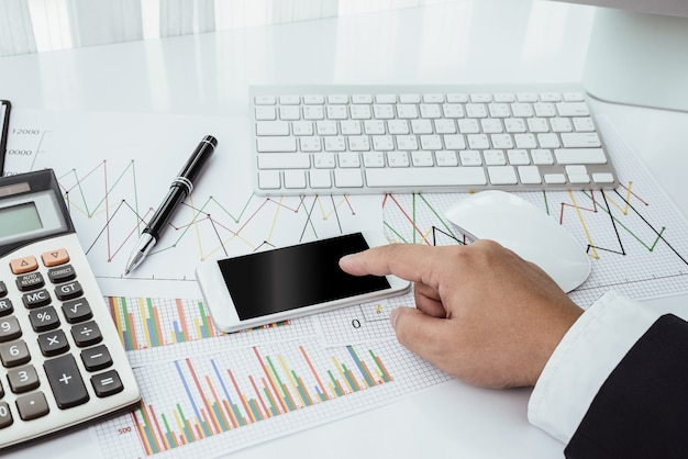 Бизнесмен работает с современными устройствами, компьютером и мобильным телефоном