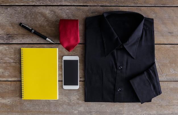 シャツ、ネクタイ、スマートフォン、ノートブック、木製の背景のペン