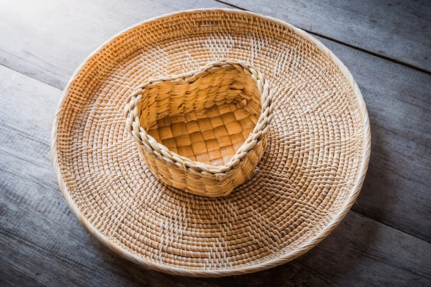 ハート型の籐のバスケットとトレイの木製の背景
