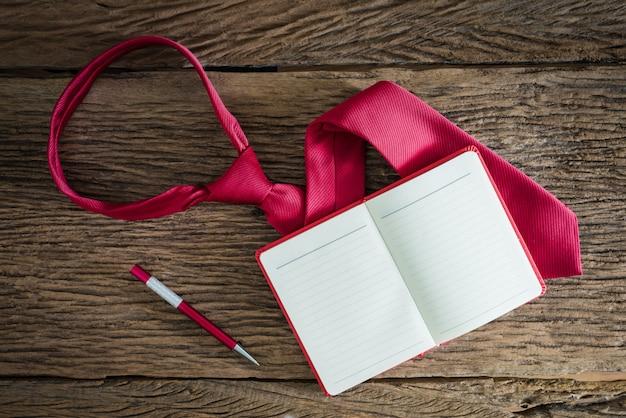 メモ帳、ペン、汚れた木の表面に赤いネクタイ