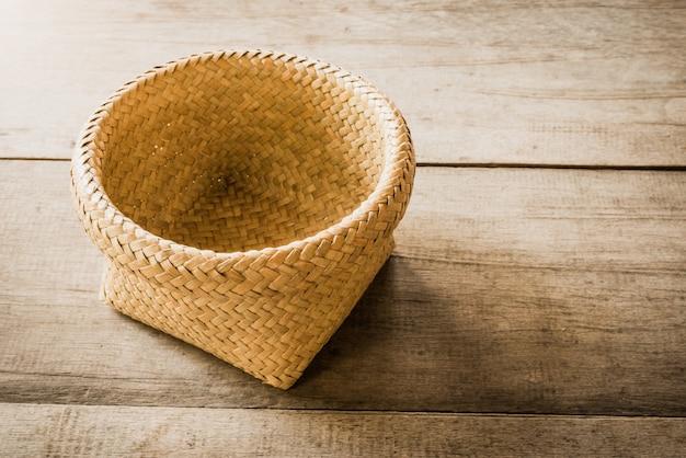 Пустая плетеная корзина на деревянном фоне