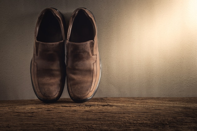 グランジの壁に木製の卓上に紳士靴のある静物