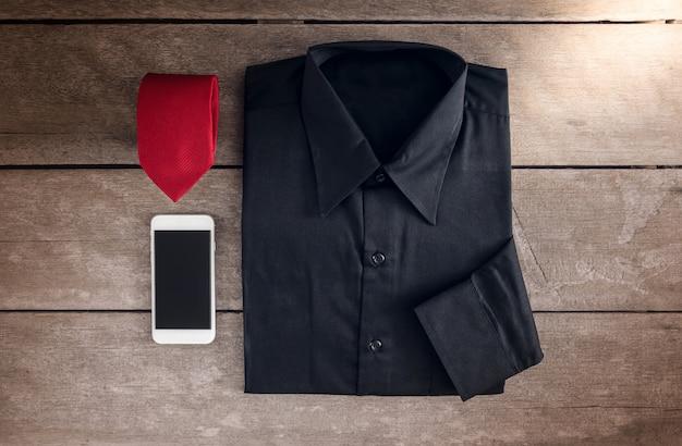 シャツ、ネクタイ、木製の背景にスマートフォン