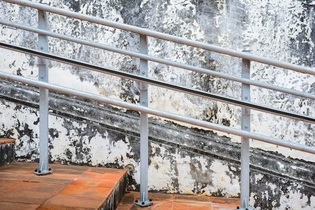 古い鋼の手すりと古いセメントの壁