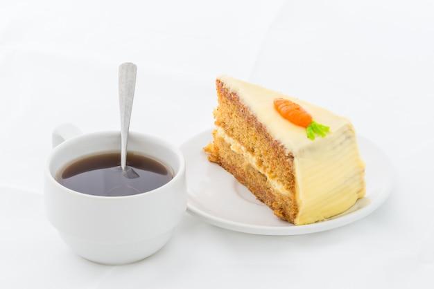 Морковный торт на белом блюде с горячим напитком