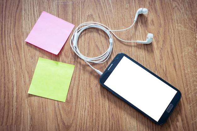黒いスマートフォン、ヘッドホン付き白いスクリーン、木製の表面に付箋