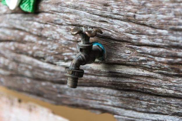木製の壁に真鍮の蛇口
