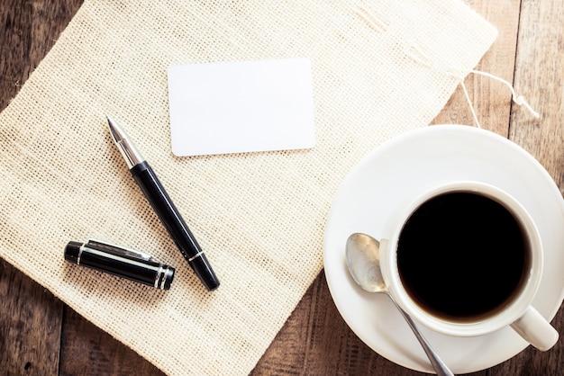 空のカード、ペンとコーヒーのカップ
