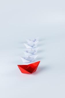 Красный бумажный кораблик лидирует среди белых