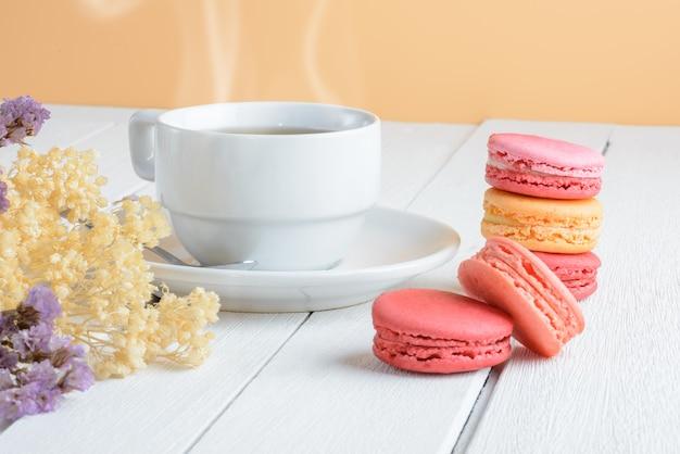 白い木製の背景に熱いお茶のカップとマカロンの種類の色