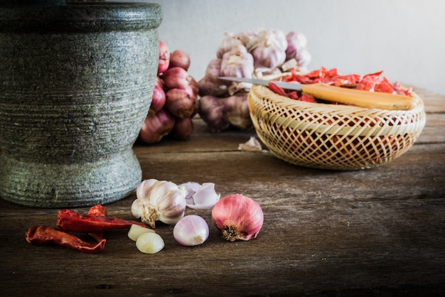 乾燥唐辛子と赤玉ねぎとニンニクと石のモルタル、古い木製の背景