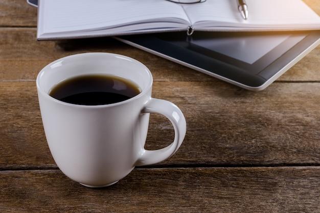 コーヒーと木製のデスクトップで作業場所をマンします。