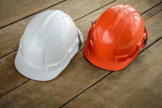 エンジニアまたは労働者としての労働者の安全プロジェクトのための白、オレンジ色のハードヘルメット