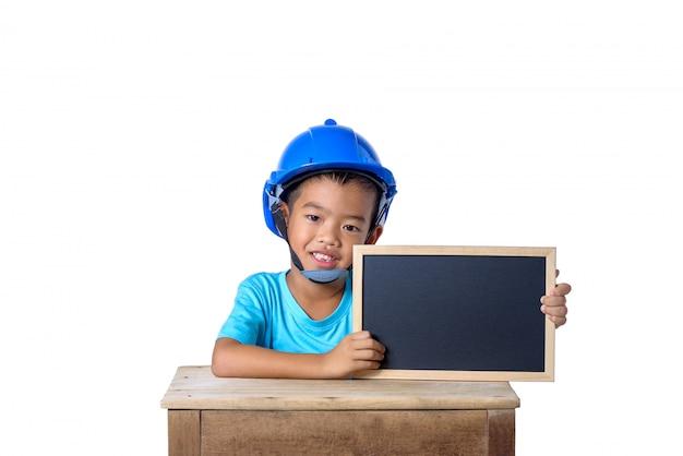 アジアの子供たちが安全ヘルメットを着用し、白い背景で隔離の黒板に笑みを浮かべて。子供と教育の概念