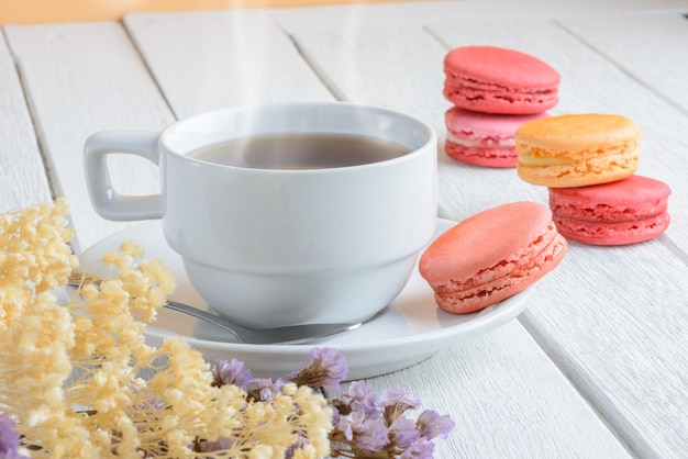 白い木製の背景に熱いお茶のカップとマカロンのさまざまな種類の色