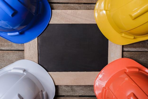 黒板と黄色、オレンジ、白、青の保護安全ヘルメット