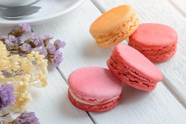 Разные виды цветных миндальных печений с чашкой горячего чая