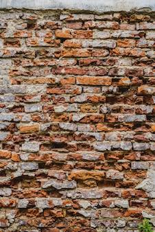 Старые руины кирпичной стены с трещинами бетона