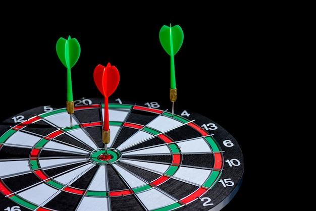 ターゲットセンターを打つ赤と緑のダーツ矢印は分離されたダーツボード