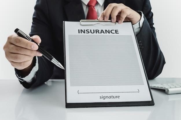 若い男のスーツで彼のオフィスで保険証を示して、ペンで指している