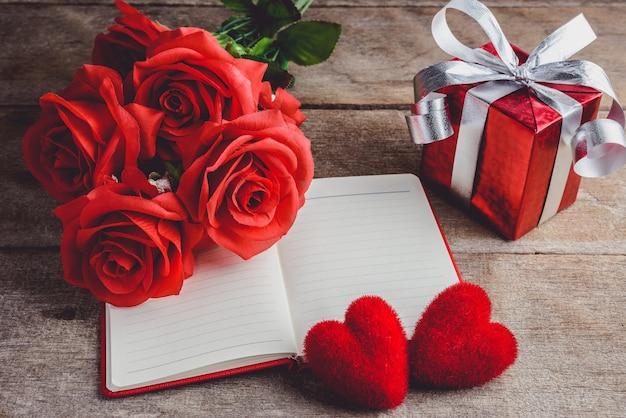 赤いバラ、赤い心、ノートブック、木製の背景にギフトボックス