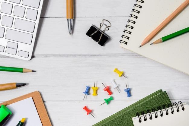 コーヒー、ノート、ペン、マーカーのカップを持つ木製の白いオフィスの机のテーブル。