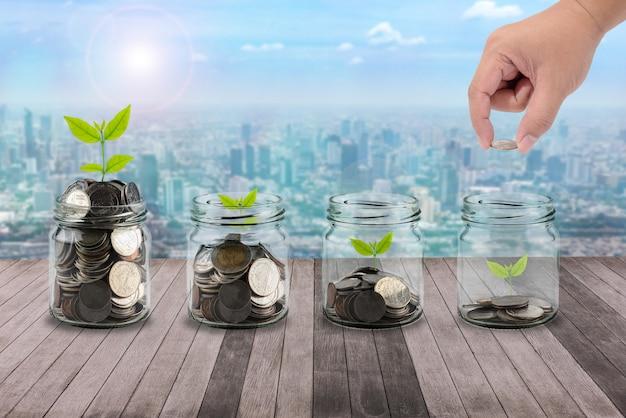 男性の手は、クリアボトル、木の上に小さな木を置くお金のコインを置くプランクの概念のビジネス