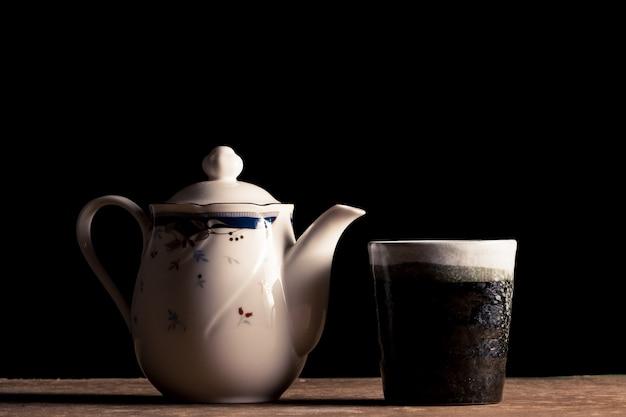 Керамический чайный горшок и чашка чая на столе, черный фон.