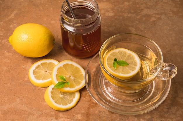Чашка чая с лимоном и медом на фоне коричневый гранж.